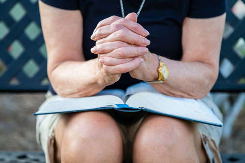 Person on bench in prayer with Bible